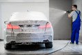 Worker covering automobile with foam at car wash - PhotoDune Item for Sale