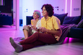 Smiling couple holding gamepads playing video game at home. Low angle shot of young people spending - PhotoDune Item for Sale