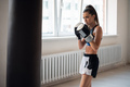 A pretty kickboxer girl is preparing for competitions in the boxing hall, practicing the technique - PhotoDune Item for Sale