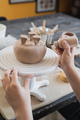 Close up of female potter holding stick and making ornament on earthenware. Clay master moulding - PhotoDune Item for Sale