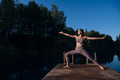 Beautiful young woman performing a spiritual yoga pose on a forest lake at sunny day, sunrise zen - PhotoDune Item for Sale
