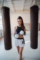 Cute girl posing for a photo in boxing gloves on the background of punching bags - PhotoDune Item for Sale
