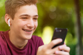 Happy teenage boy is using mobile phone, outdoors. - PhotoDune Item for Sale