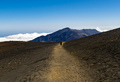 Woman Walking in the Crater of a Volcano with View of Mountains and Clouds.Haleakala National Park - PhotoDune Item for Sale