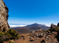 Person Standing on a Stone with a View of Crater and Clouds in Haleakala National Park - PhotoDune Item for Sale