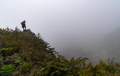 Woman with Backpack on Top of a Mountain with Fog - PhotoDune Item for Sale