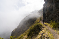 Woman Walking on a Path to the Edge of a Foggy Mountain - PhotoDune Item for Sale