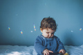 Little baby playing with a smart phone in a blue room - PhotoDune Item for Sale