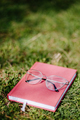 glasses and notebook lay on grass - PhotoDune Item for Sale