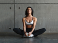 sporty woman in sportswear in lotus pose near concrete wall - PhotoDune Item for Sale