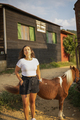 Placeit - Beautiful Young Woman in Countryside at a Horse Farm and Posing in Front of a Pony Horse - PhotoDune Item for Sale