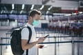 Man wearing face mask and holding smart phone with passport at airport - PhotoDune Item for Sale