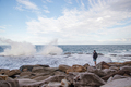 Man Standing on a Rock Taking a Picture of the Sea whit the a Phone - PhotoDune Item for Sale
