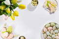 Easter table setting with a plate of colored pastel eggs, a bouquet of tulips and biscuits rabbits - PhotoDune Item for Sale