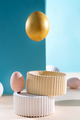 Easter background. Levitating Easter golden egg composition and white eggs on a blue background - PhotoDune Item for Sale