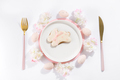 Gingerbread easter cookies on a plate, next to cutlery, and pink eggs with flowers - PhotoDune Item for Sale