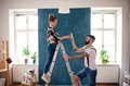 Mid adults couple changing light bulb indoors at home, relocation and diy concept - PhotoDune Item for Sale