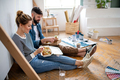 Couple eating lunch indoors at home, relocation, diy and food delivery concept - PhotoDune Item for Sale