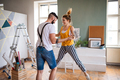 Couple having fun when painting wall indoors at home, relocation and diy concept - PhotoDune Item for Sale