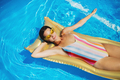 Top view of young woman in swimming pool outdoors on floating bed, relaxing - PhotoDune Item for Sale