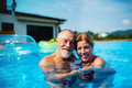 Cheerful senior couple in swimming pool outdoors in backyard, looking at camera - PhotoDune Item for Sale