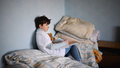 Poor sad small girl on bed indoors at home, poverty concept - PhotoDune Item for Sale