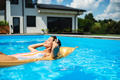 Young woman in swimming pool outdoors in backyard garden, relaxing - PhotoDune Item for Sale