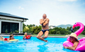 Group of cheerful seniors in swimming pool outdoors in backyard, jumping - PhotoDune Item for Sale