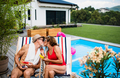 Senior couple in love sitting by swimming pool outdoors in backyard, kissing - PhotoDune Item for Sale