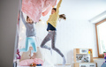 Two small girls sisters indoors at home, jumping on bed in bedroom - PhotoDune Item for Sale