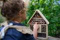 Rear view of small girl playing with bug and insect hotel in garden, sustainable lifestyle - PhotoDune Item for Sale