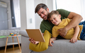 Happy father and son playing with digital tablet at home - PhotoDune Item for Sale