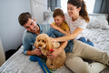 Happy young friendly family spending fun times together and cuddling with their pet at home - PhotoDune Item for Sale