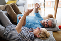 Beautiful happy mature couple is using a digital tablet, talking and smiling at home - PhotoDune Item for Sale