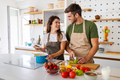 Young happy couple is enjoying and preparing healthy meal in their kitchen - PhotoDune Item for Sale