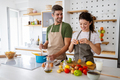 Happy young couple preparing food in kitchen at home - PhotoDune Item for Sale