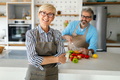Happy senior couple cooking together and having fun in home kitchen - PhotoDune Item for Sale