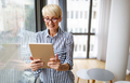 Happy retired senior woman relaxing at home, using digital tablet - PhotoDune Item for Sale