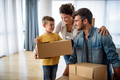 Happy family with children moving with boxes in a new apartment house - PhotoDune Item for Sale