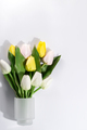 Close-up of a beautiful bouquet of white and yellow tulips in a glass vase on white background - PhotoDune Item for Sale