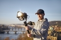 Man filming with camera and gimbal against urban skyline - PhotoDune Item for Sale