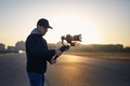 Man filming with camera and gimbal against city at sunrise - PhotoDune Item for Sale