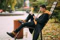 Young man sitting on a bench in park and listening to music - PhotoDune Item for Sale