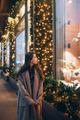 Woman by illuminated showcase on city street - PhotoDune Item for Sale