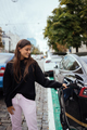 Woman near electric car. Vehicle charged at the charging station - PhotoDune Item for Sale