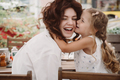 Portrait of little daughter kissing her beautiful happy mother - PhotoDune Item for Sale