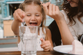 Little girl with mom playing with ice cubes in a cozy cafe - PhotoDune Item for Sale