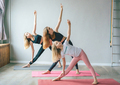 Three white teenage girls sisters in sports leggings stand in a yoga pose on the mats in the gym. - PhotoDune Item for Sale