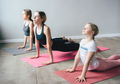 Three teenage girls sisters in sportswear doing yoga and stretching on mats in the gym. - PhotoDune Item for Sale