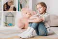 lonely little child sitting on floor in front of shelves with toys and looking at camera - PhotoDune Item for Sale